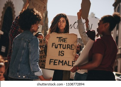 Women protesters hold up signs of the future is female. Group of women protesting outdoors for female empowerment.