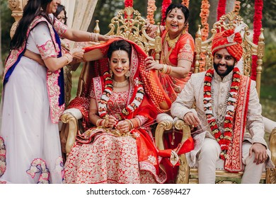Women put a cloth on Indian bride's head while she sits with groom dressed in sherwani during the ceremony