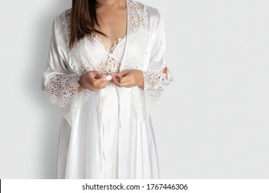 Women put on white sexy nightgown & long sleeve satin robe with floral lace, A girl trying on new white nightwear for sleep. Light gray empty space on right side
