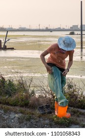 Women putting on waders to go into the wetlands. The waders are green with florescent boots. She stand on the edge of the wetlands. She has a coral colored top and blue round hat.