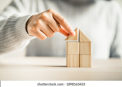 women putting triangle wooden block for show the construction of a wooden in the shape of a house, Build a home concept.