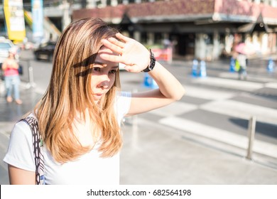 A women raise her hand to cover the sunlight.