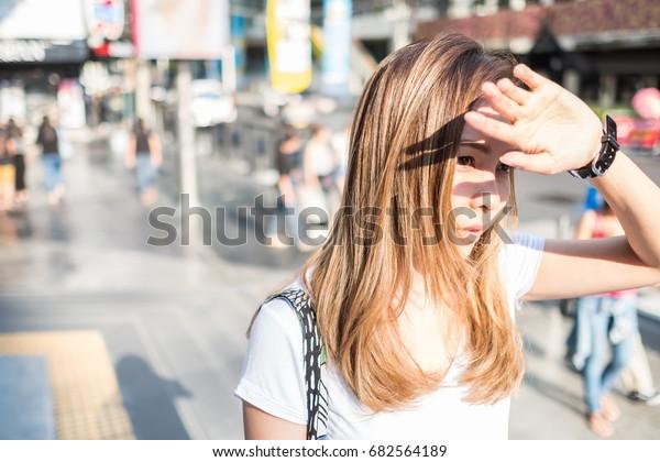 女が手を上げて日光を遮る。