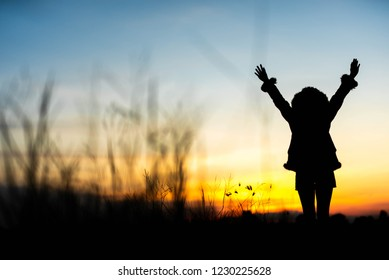 Women raise their hands happily at sunset.