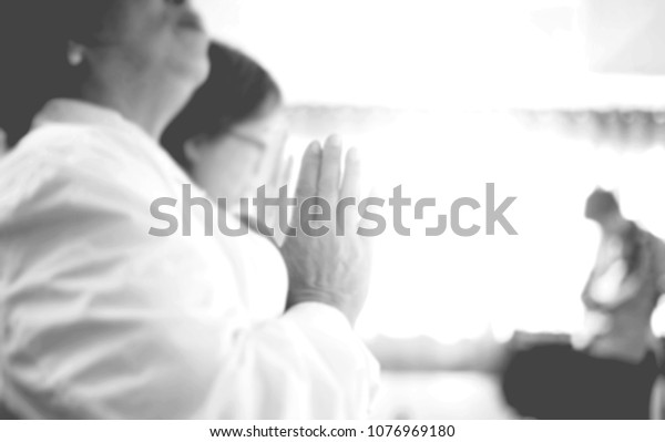 Women raise their hands to pray for God's help in the church.