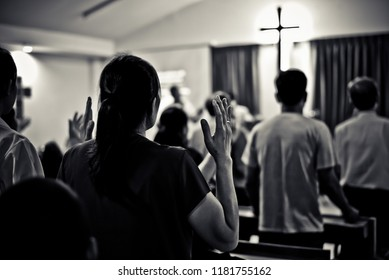 Women raise their hands to surrender to God.