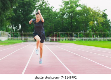The women ran very fast in the treadmill in the stadium.