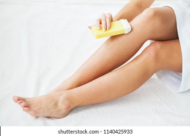 Women receive waxing for hair removal in her bathroom.