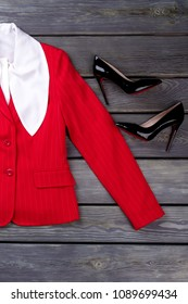 Women red blazer and black louboutin. Set of female elegant clothes on rustic wooden background, top view.