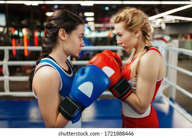 Women in red and blue gloves boxing on the ring