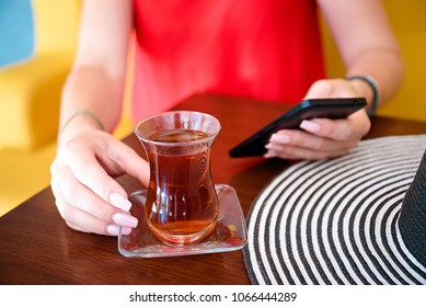 women in red dress and hand with phone and turkish tea and hat on the wooden table.