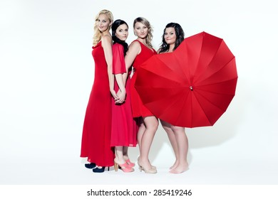Women in red dresses and red umbrella in the shape of heart