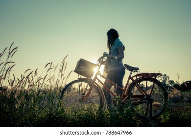 Women relaxing with a bike in the meadow at sunset.