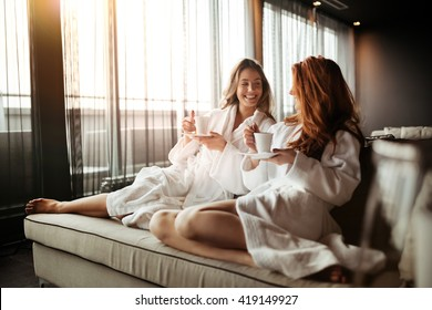 Women relaxing and drinking tea in robes during wellness weekend - Shutterstock ID 419149927