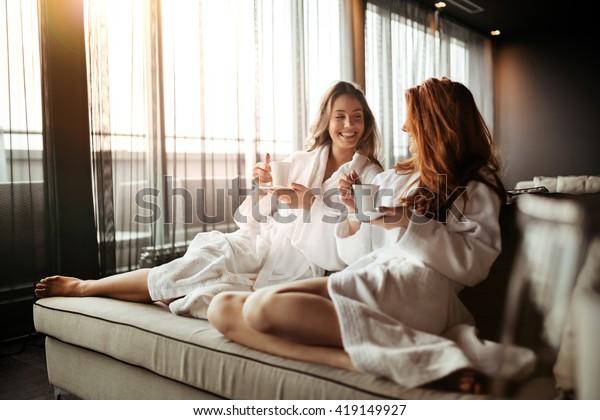 Frauen, die sich entspannen und Tee in Roben trinken während des Wellness-Wochenendes