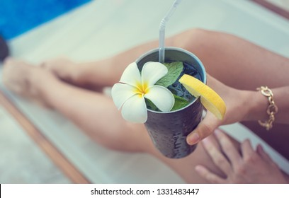 Women relaxing near luxury swimming pool with exotic cocktail