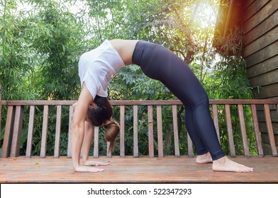 Superb Women Relaxing In Yoga Bridge Pose On Wooden Terrace With Warm Light Effect  In The Morning