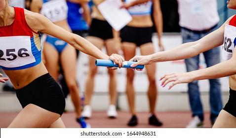 women relay team passing of baton running 4x400 meters