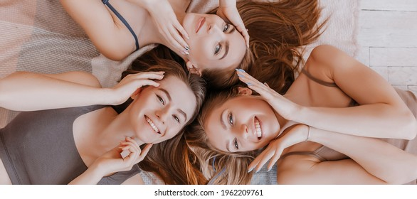 Women rest and have fun. Girlfriends laugh at home lying on the floor on pillows. Tree girls make homemade face and hair beauty masks. Women take care of youthful skin.