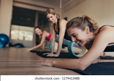 Women resting their abdomen on yoga or pilates wheel at the gym. Happy women doing pilates workout at the gym.