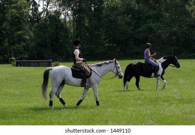 women riding horses in field