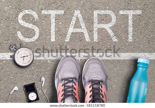 Women Running shoes and run equipment on asphalt whit start inscription. Running training on hard surfaces. Runner Equipment stopwatch and music player, plastic water bottle. Asphalt on background.