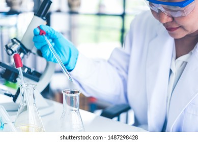 Women scientist looking through microscope in laboratory. Women scientist doing some research with dropper chemical testing.