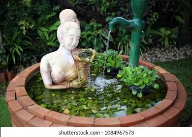 Women sculpture with water flow fountain. Women statue decoration in the garden pond.