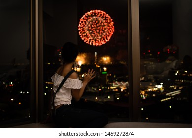 Women see the fireworks from the window of the apartment