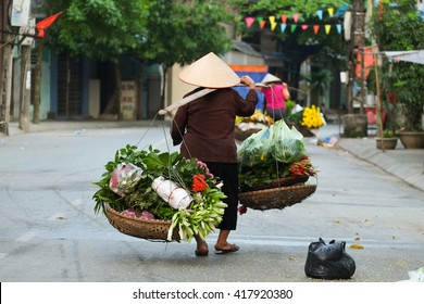 Women selling flowers in the early morning in a small market, Hanoi, Vietnam. Life of florist vendor in Hanoi, Vietnam.
