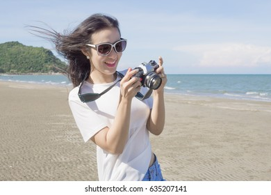 Women are shooting on the beach.
