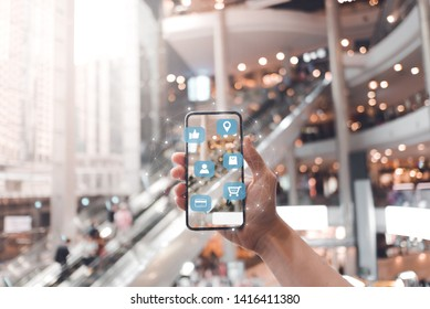 Women in shopping mall using mobile phone with shopping application and social media.