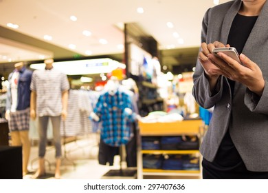 Women in shopping mall using mobile phone.