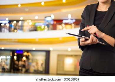 Women in shopping mall using mobile Tablet PC.
