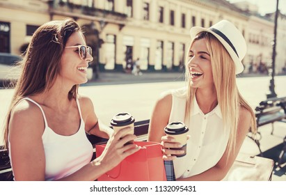 Women in shopping. Two beautiful women sitting on the bench after shopping, drinking coffee and enjoying in conversation. Consumerism, shopping, lifestyle concept