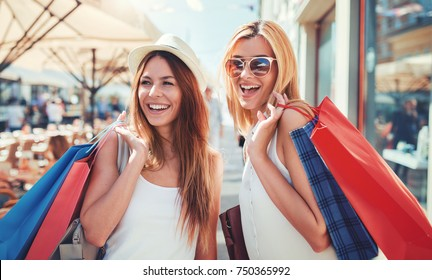 Women in shopping. Two happy women with shopping bags enjoying in shopping. Consumerism, shopping, lifestyle concept