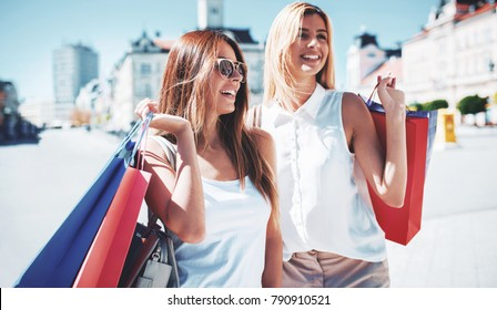 Women in shopping. Two happy women with shopping bags enjoying in shopping, haning fun in the city. Consumerism, shopping, lifestyle concept