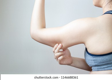Women show her fat arm close up isolated on white background.  Concept of unhealthy lifestyle.