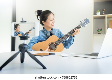women sing a song with guitar in hands use camera to broadcast live video to social network by internet at home