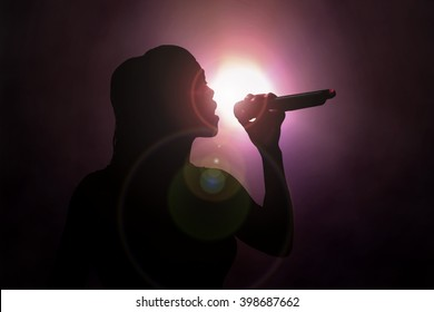 Women singing under spotlight