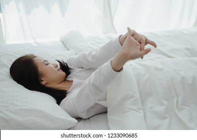 women sit at the edge of the bed. And stretching his arms to relax in the morning.Wake up in the morning.Warm tone.Do not focus on the object.