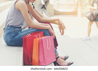 Women sit on stairs during shopping season with shopping bags