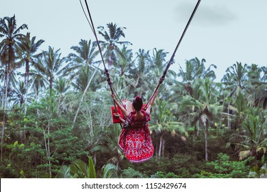 Women sit on swings at a height of more than twenty meters. In Indonesia Bali Province.