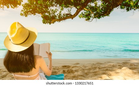 Women sit and reading a book under the tree at seaside. Back view of sexy Asian woman with straw hat relaxing and enjoying holiday at tropical paradise sand beach. Summer vacation. Summer vibes.