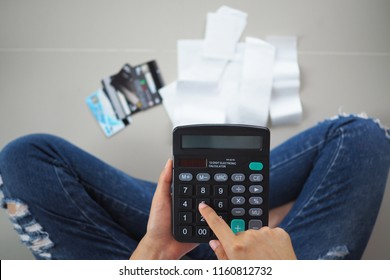 Women sit stressed with the calculator calculates receipts expenses. To repay credit card debt.