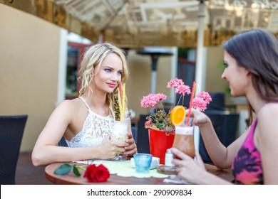 Women sit under parasol in restaurant, drink cocktail on summer day