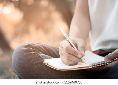 women siting and writing memory on notebook in park in summer