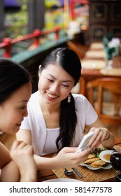 Women sitting in cafe, looking at mobile phone