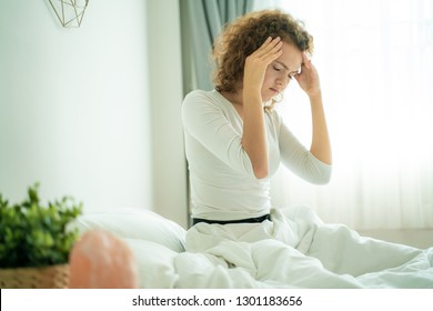 Women sitting on bed holding her head have a headache with migraine
