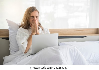 Women sitting on the bed using a laptop notebook check mailbox Or blogging and sneezing to become sick with the flu in morning at apartment.